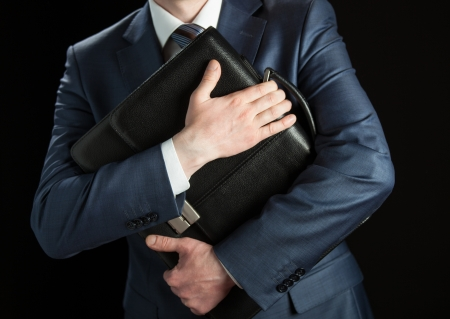 Businessman clasping briefcase to his breast on black background photo