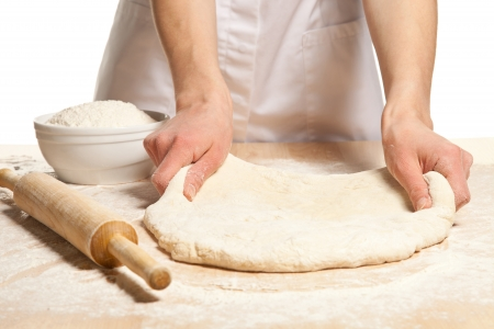 Hands stretching dough on wooden table; white background