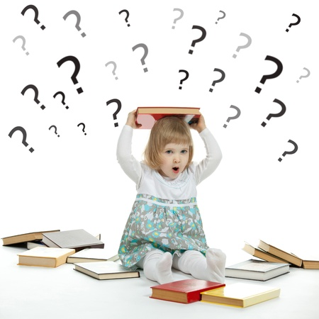 Scared little child sitting on the floor surrounded by books and question marks photo