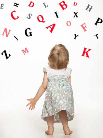 Little baby girl catching letters of alphabet Stock Photo