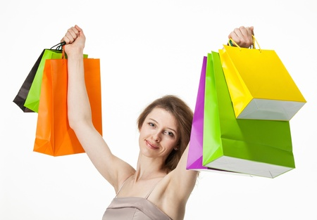 Attractive girl holding multicolored shopping paper bags - closeup shot on white background Stock Photo - 19340835