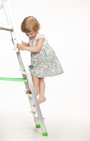 The naughty little girl walking down the stepladder on white background