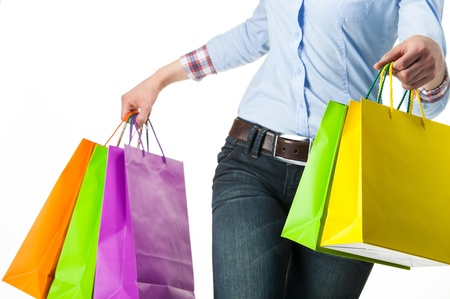Woman holding multicolored shopping paper bags - closeup shot on white background Stock Photo - 19310245