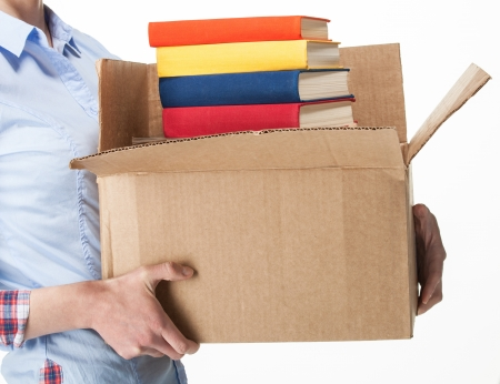 Student holding a big box with stack of books; isolated on white