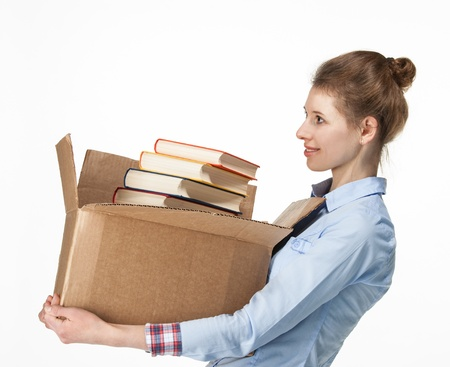 Smiling woman carrying a cardboard box with books; isolated on white photo