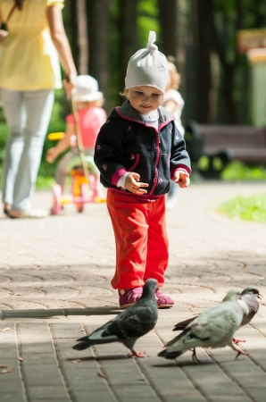 Pretty little girl looking at pigeons