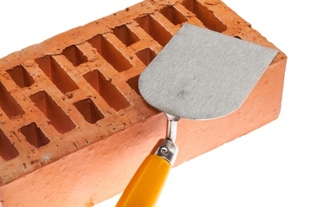 Plastering trowel and a brick isolated over white background photo