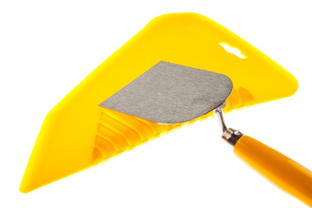 Plastic putty knife for hanging wallpapers and plastering trowel isolated over white background photo