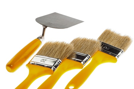 Plastering trowel and paintbrushes isloated over white background photo