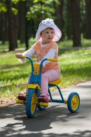 Beautiful baby girl rides tricycle in a summer park photo