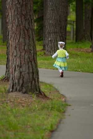 Little girl running away along a road in a park photo