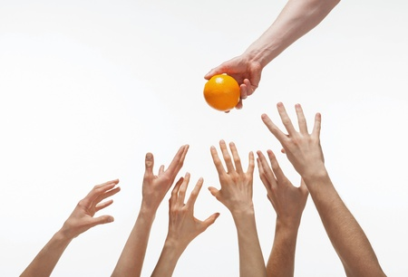 Many hands want to get orange, white background Stock Photo