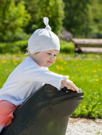 pat: Baby girl sitting on a stone frog in a park Stock Photo