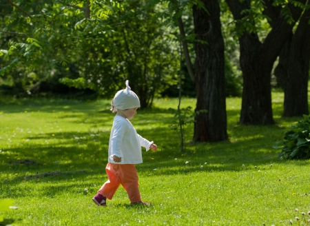 Little girl going firm step on the grass photo