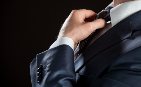 Businessman adjusting his tie - closeup shot