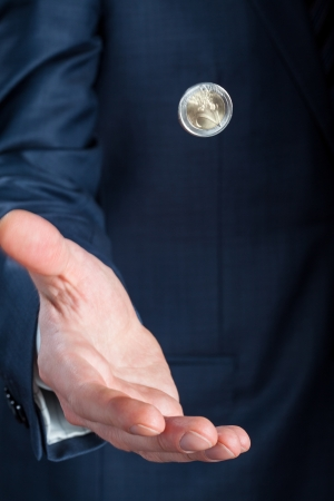Businessman flipping a coin - closeup shot photo