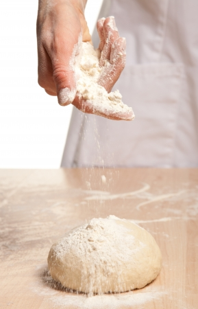 Womans hand meals dough on wooden table; white background photo