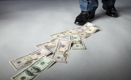 Mens feet and dollar banknotes on the floor
