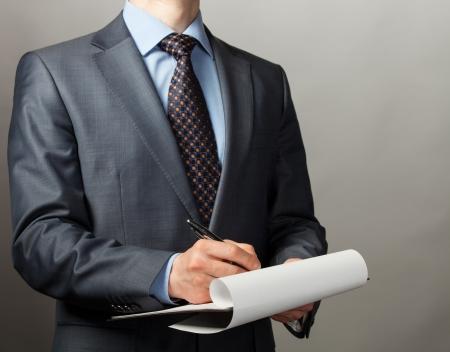 Zakenman het maken van aantekeningen op het papier, grijze achtergrond
