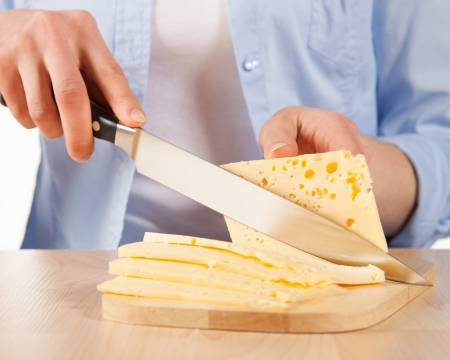 Cutting into pieces  fresh cheese photo