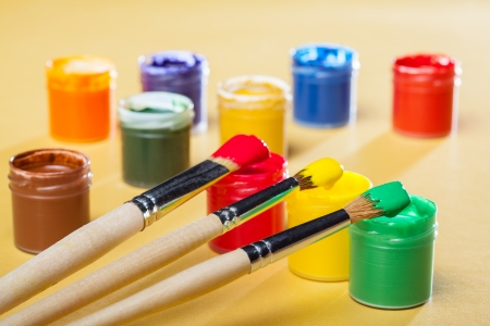 paintbox: Gouache paints and brushes on yellow background Stock Photo