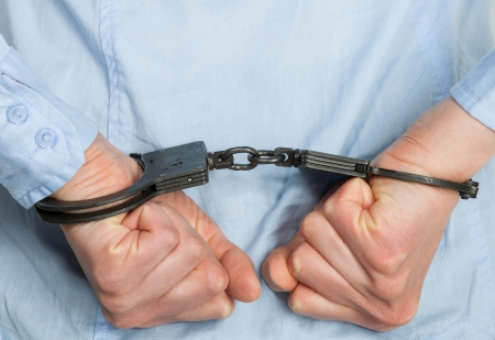 Hands in handcuffs on white background photo