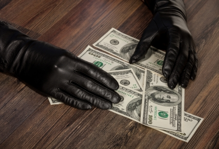Human hands in black gloves holding dollars photo