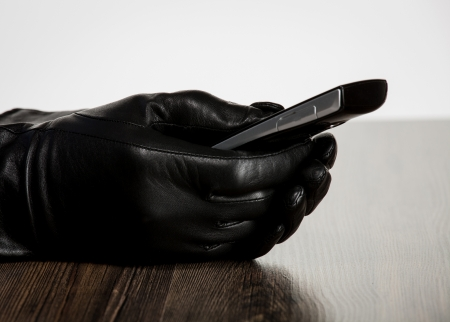 Hand in black leather glove holding cellphone photo