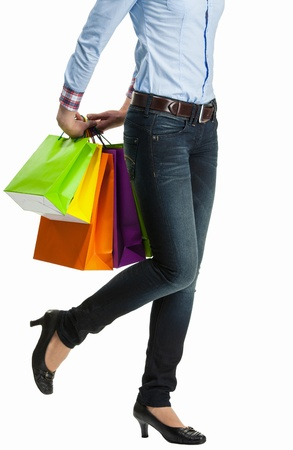 Woman hiding multicolored shopping paper bags isolated on white photo