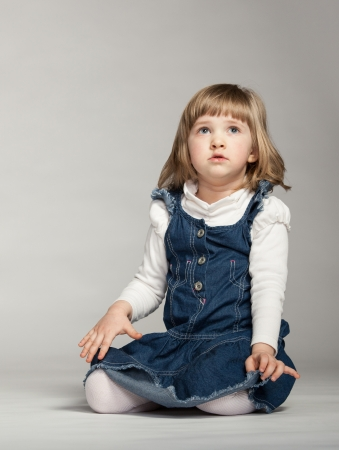 concetrated: Little girl looking up and sitting on the floor, on dark background