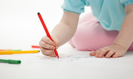 baby drawing: Baby girl drawing with colorful pencils on white background