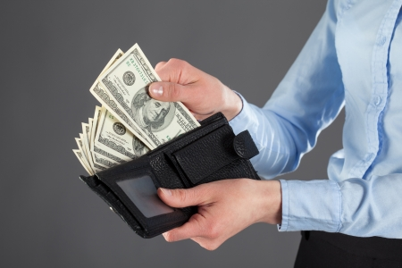 : Womans hands taking money out of leather wallet on dark background photo