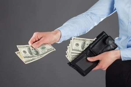 Womans hands paying money on dark background