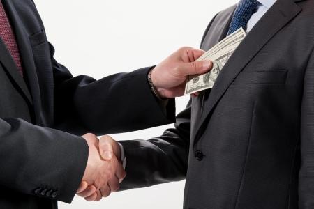 Giving a bribe into a pocket - closeup shot Stock Photo