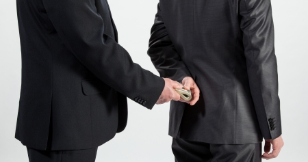 Businessman giving a bribe, neutral background photo