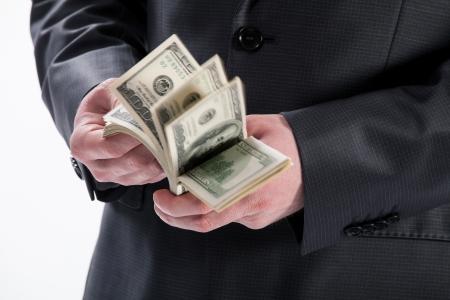 Mans hands counting dollar banknotes, closeup shot Stock Photo