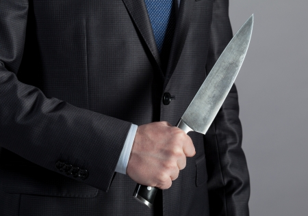confrontational: Businessman holding big knife in his hand