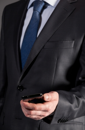 important phone call: Businessman holding cellphone - closeup shot