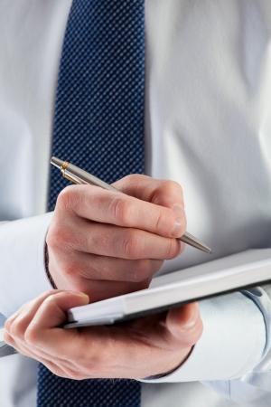 Businessman signing a contract, closeup shot photo