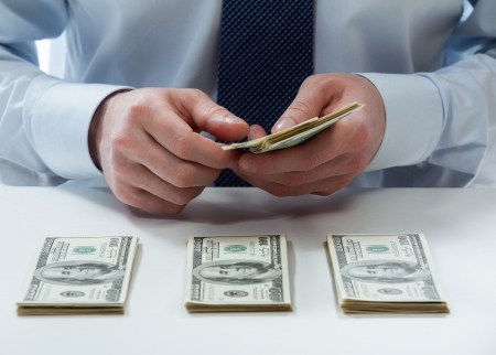 Bank teller's hands counting dollar banknotes on the table Stock Photo