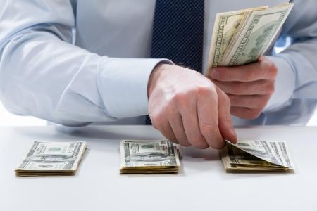 Bankbediende's handen tellen dollar biljetten op de tafel