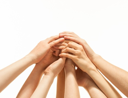 Successful team: many hands holding together on white background