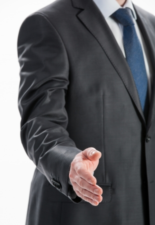 Businessman offering handshake to you on neutral background photo