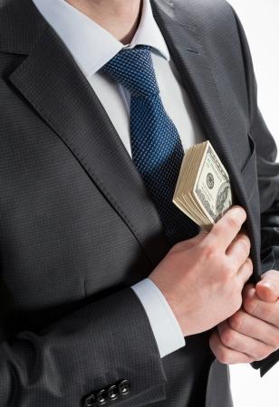 venal: Businessman putting money in his pocket - closeup shot