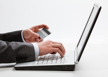 entering information: Businessman entering information from a credit card using laptop, closeup shot