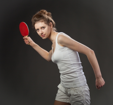 Young woman playing table tennis; dark background Stock Photo - 20904043