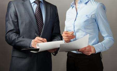Businessman signing contract/document, grey background Foto de archivo