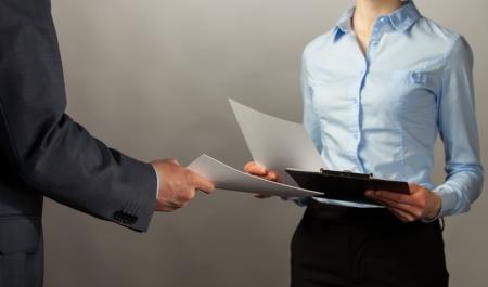 Businessman and businesswoman interchange of documents, grey background