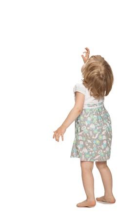 Kleine baby meisje dat iets boven haar, achteraanzicht, geïsoleerd op wit