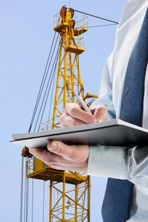 acceptance: Businessman signing acceptance report  contract, construction crane in the background Stock Photo